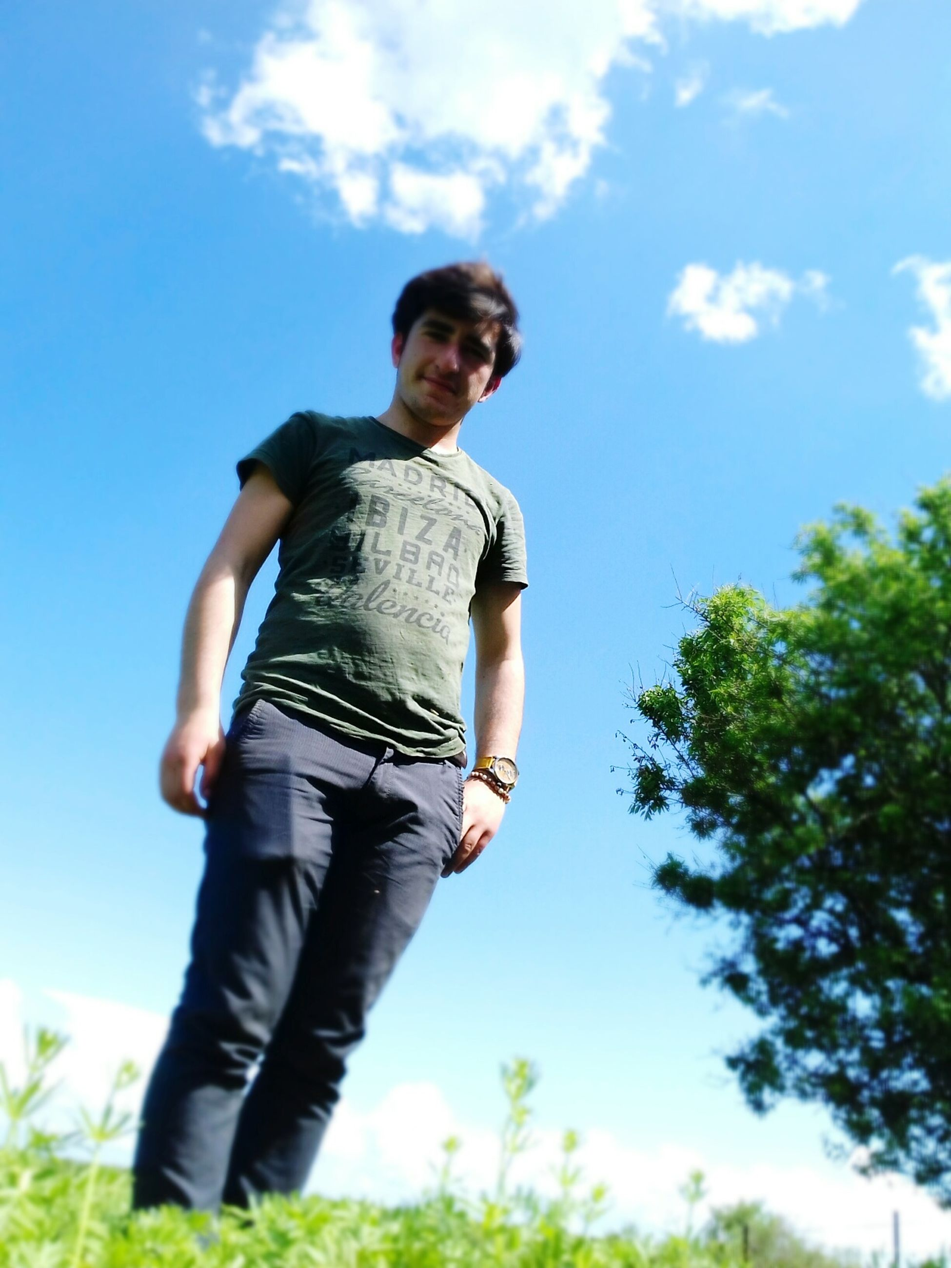 casual clothing, sky, one person, low angle view, tree, young adult, standing, real people, nature, young men, outdoors, day, blue, growth, grass, young women