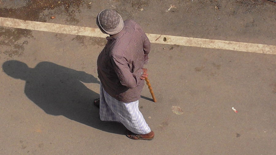 OLD MAN...WALKING WITH A WALKING STICK A New Beginning The Slow Start Of A New Walk Old Age Man No Help An Old Man Walking With Stick Low Section City High Angle View