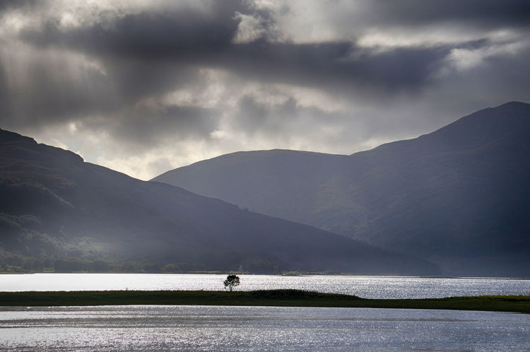 A lone tree located on an island in the middle of Loch Alsh, Highlands of Scotland Highlands Scotland Loch  Scotland Beauty In Nature Cloud - Sky Highlands Highlands Of Scotland Mountain Mountain Range Nature Non-urban Scene Outdoors Scenics - Nature Sky Tranquil Scene Tranquility Water