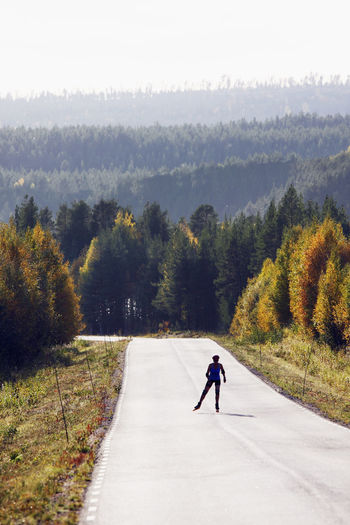 Full length of man on road amidst trees during autumn