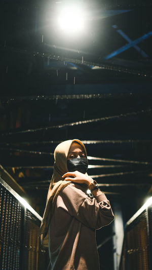 Low angle view of woman with masked at night