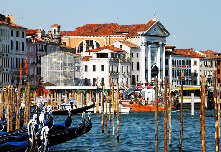 Gondolas moored on grand canal by buildings