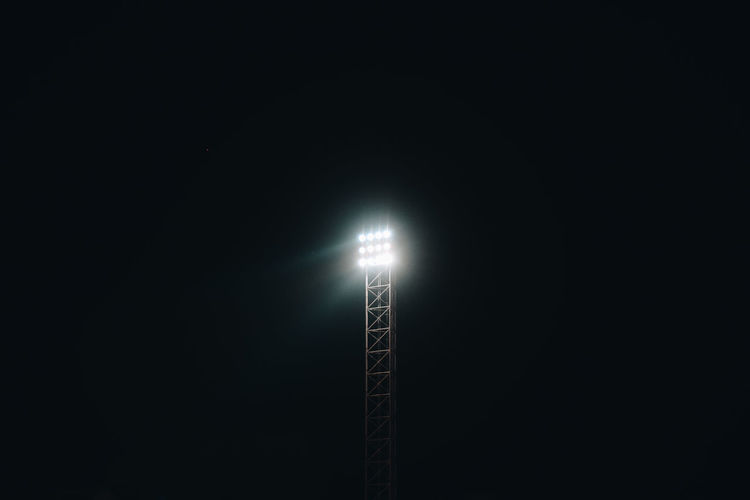 Low angle view of illuminated street light against dark sky