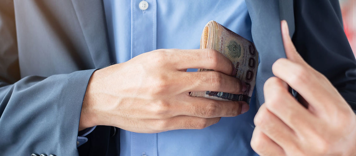 Midsection of businessman keeping paper currency in pocket
