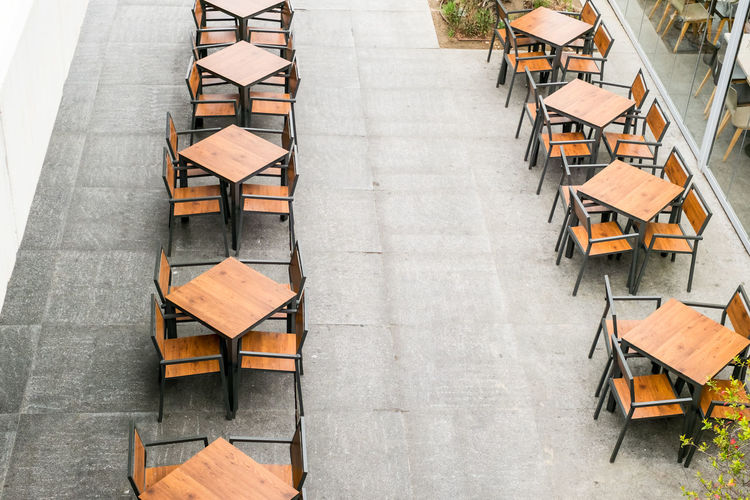tables and empty chairs at the coffee shop Tables And Empty Chairs At The Coffee Shop Table Chairs High Angle View Seat Chair Wood - Material Real People In A Row Day Large Group Of Objects Arrangement Outdoors People Men Architecture Sidewalk Cafe Book Absence Empty