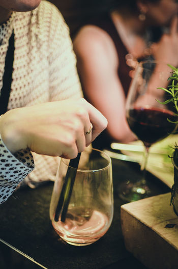 Real People Drink Human Hand Refreshment Hand Food And Drink Holding Alcohol Midsection One Person Table Wine Glass Indoors  Human Body Part Wineglass Glass - Material Container Food Red Wine