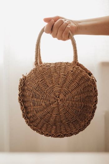 Close-up of hand holding wicker basket