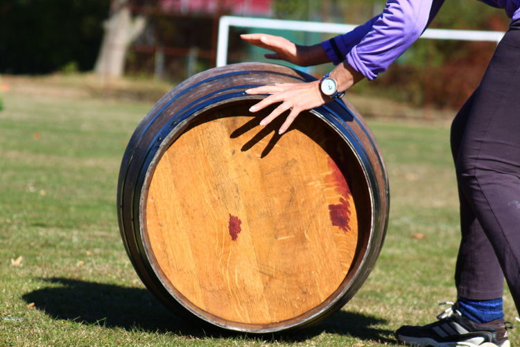 Low section of man pushing wine cask on grassy field