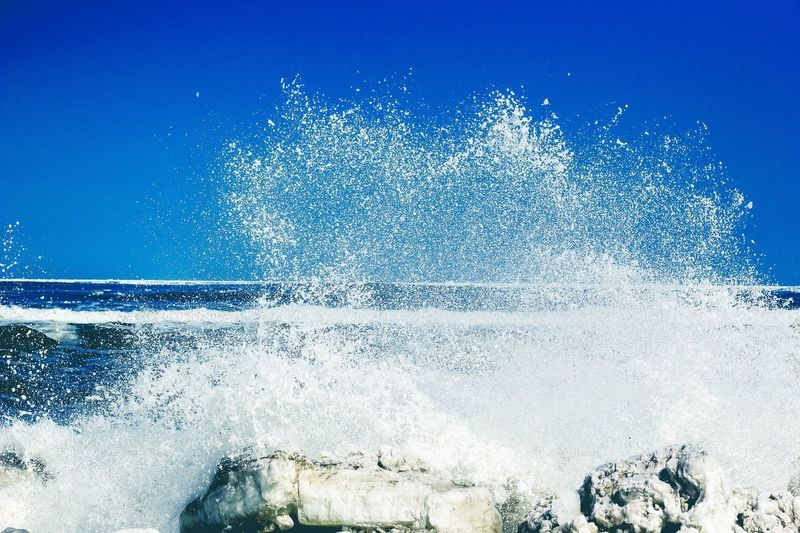 Water splashing in sea against clear blue sky