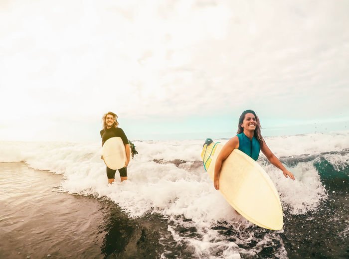 Friends carrying surfboards while walking in sea