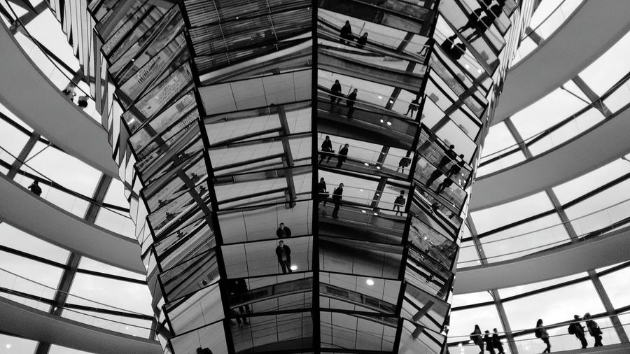 Reflection of people on glass in sir norman foster building