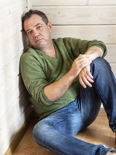 Portrait of depressed mature man sitting on hardwood floor at home