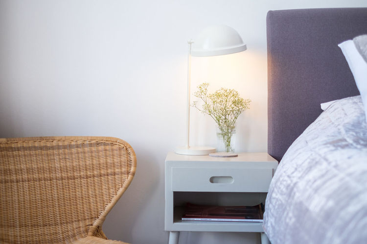 Illuminated desk lamp on night table at home