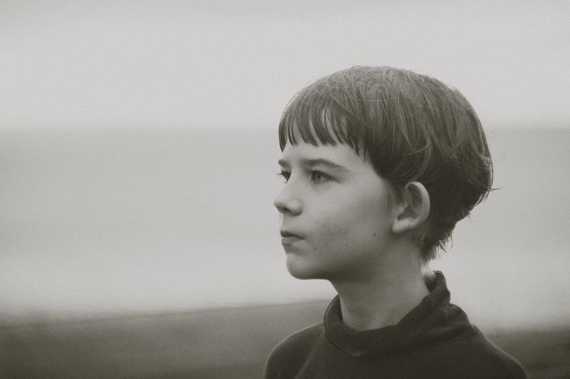 Close-up of thoughtful boy looking away during foggy weather