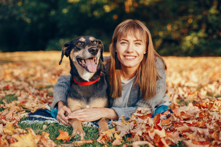 Portrait of woman with dog during autumn