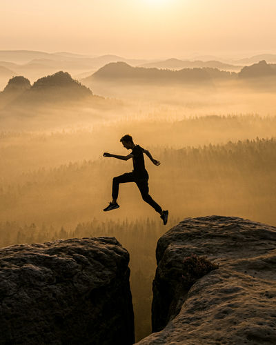 Full length of man jumping on rock against sky