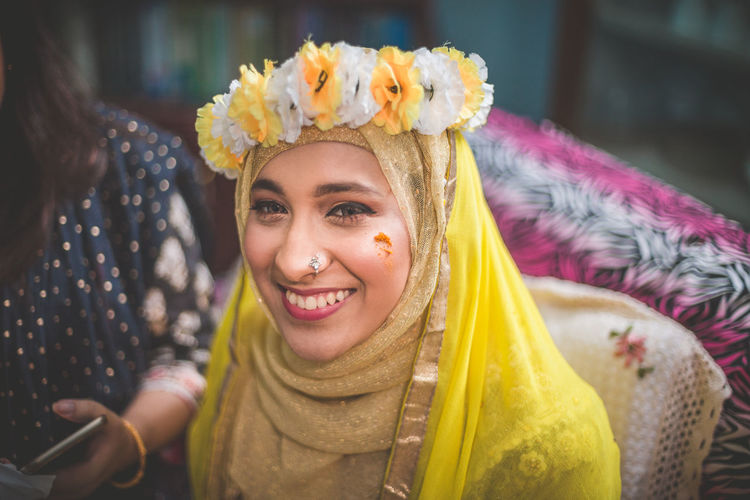 Portrait Of Smiling Young Woman In Traditional Clothing And Flowers At Home