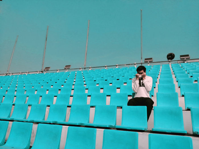 An unknown person sitting on blue seat at stadium