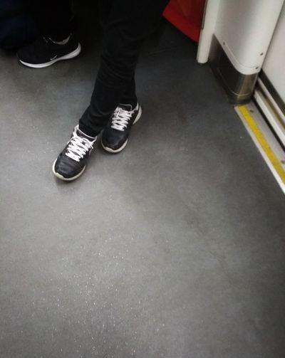 Taking the public transport to work. Walking Shoes Sneekers Cross Legs Low Section Men Human Leg Shoe Street Scene