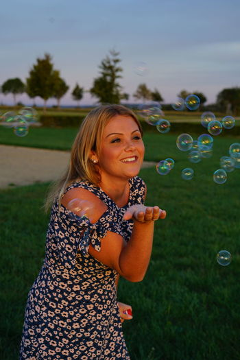 Smiling young woman blowing bubbles while standing on grassy field in park during sunset