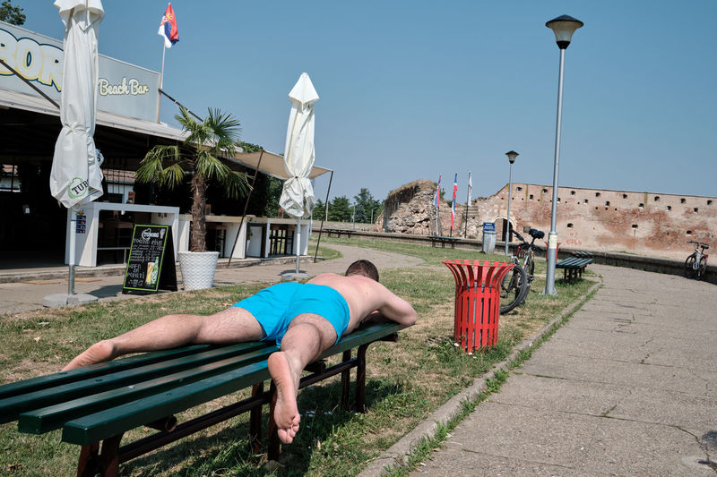 Man lying on bench by street against sky