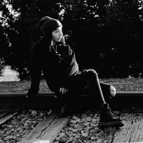 Full length of teenage girl looking away while sitting on railroad track