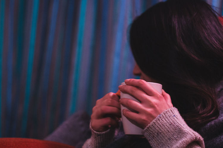 Close-Up Of Woman Relaxing While Holding Coffee Cup At Home During Winter