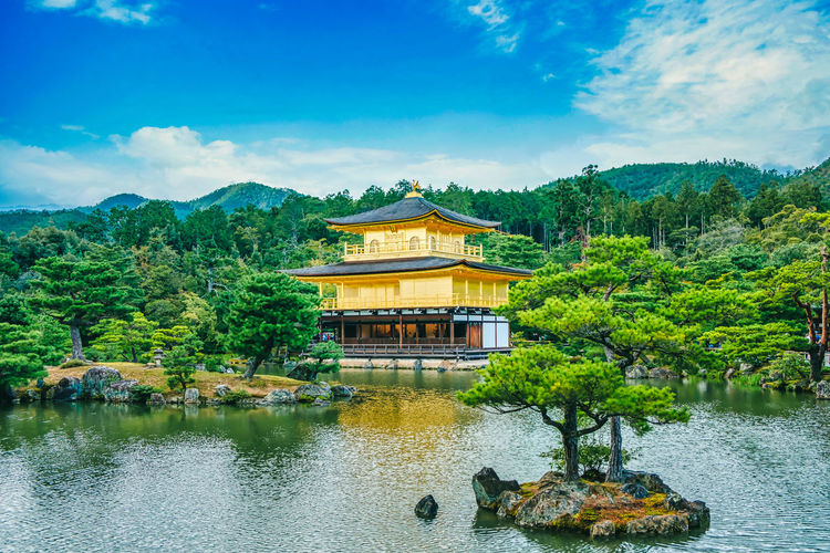 Famous golden temple in kyoto by lake and against sky