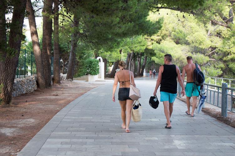 Rear view of people walking on footpath