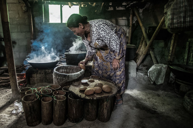 Woman preparing food while standing by wood burning stove