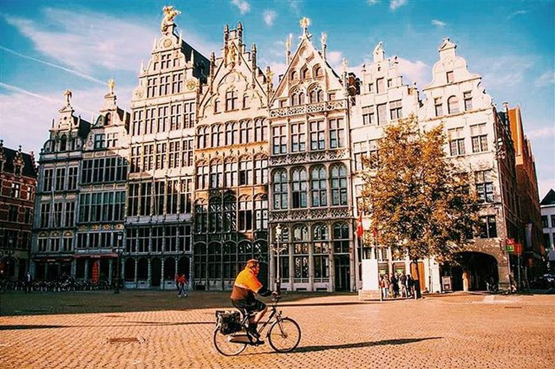 A Bicycler passes through the Antwerp Skyline of Flemmish Renaissance Buildings . Antwerpen Antwerpfashion Artinthecity Colors Cityhall Citylife City Sky Bikelife Bike Belguim Belgian  Architecture Art Antwerpe Photooftheday Photojournalism Photo glimpse oneplusx onthemove ©saranshsehgal
