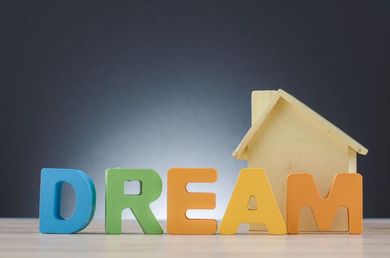 mortgage and new home concept, word DREAM over house miniature and blue background Still Life Toy Block Alphabet Indoors  Multi Colored Letter Text Toy Wood - Material Childhood Capital Letter Studio Shot Education Learning Table Copy Space Western Script Group Of Objects