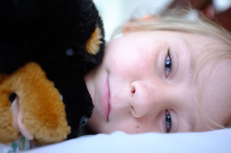 Close-Up Portrait Of Girl Relaxing With Stuffed Toy On Bed