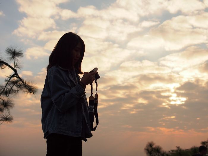 Silhouette Woman Photographing While Standing Against Cloudy Sky During Sunset