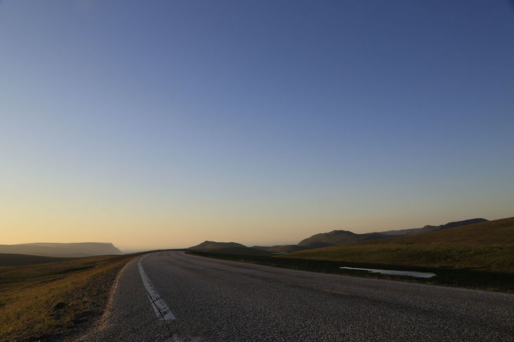 Empty road against clear sky during sunset