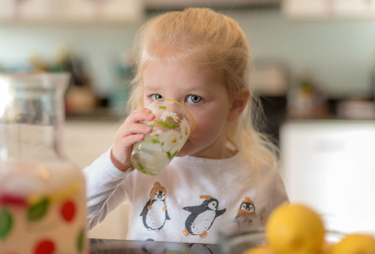 Portrait of cute girl drinking juice at home