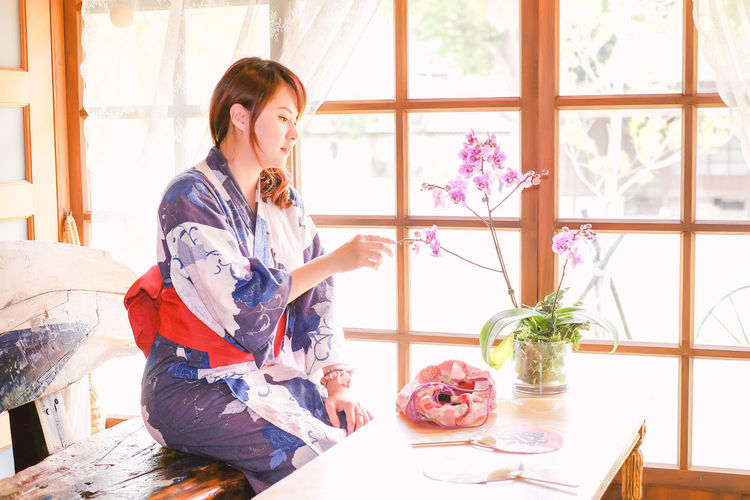 Young woman in kimono looking at orchid vase at home