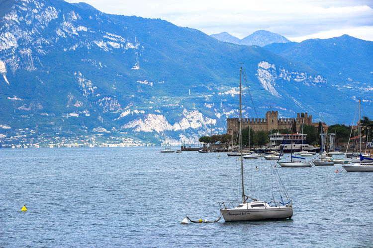 The yacht on the background of the fortress and the mountains in Lake Garda, Italy Background Bastion Culture Entertainment Europe Fortress History Italy Lago Del Garda Lake Lake View Military Mountain Mountain Range Nautical Vessel Tourism Traveling Tree Trip Vacation Voyage Water Waterfront Yacht