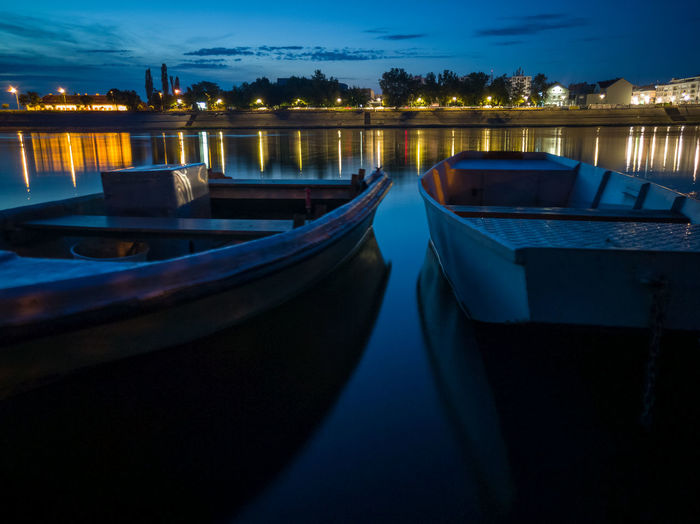 Boats moored in sea at night