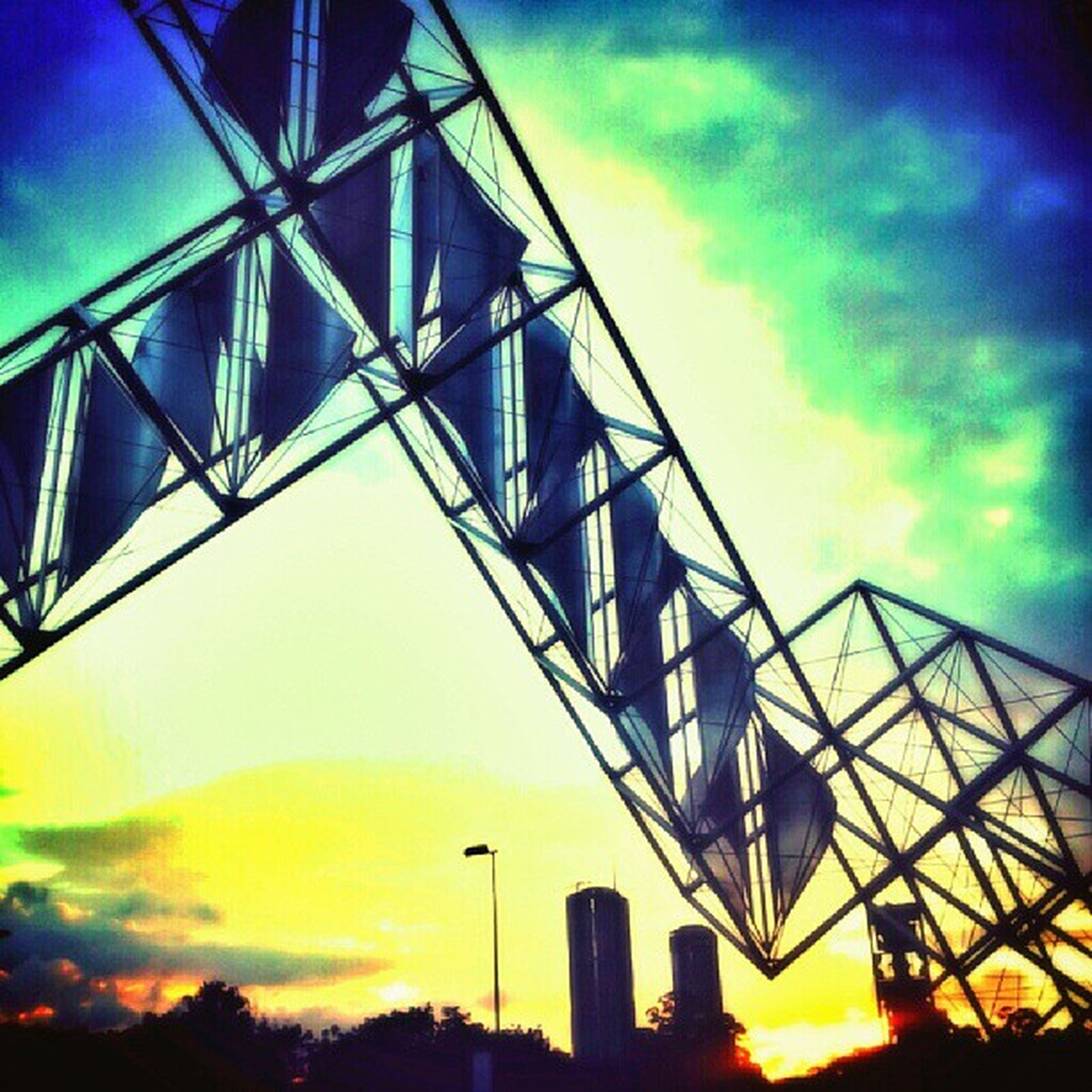 low angle view, sky, built structure, architecture, cloud - sky, sunset, silhouette, cloud, metal, no people, outdoors, orange color, cloudy, dusk, connection, modern, yellow, arts culture and entertainment, engineering, sunlight