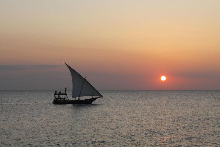 Dhow at sunset in Zanzibar Tanzania Zanzibar Dhow Horizon Over Water Sailboat Sailing Sunset Sunset Over Water