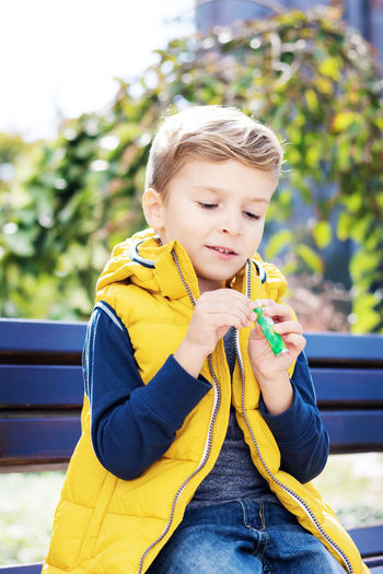 Boy holding yellow while sitting outdoors