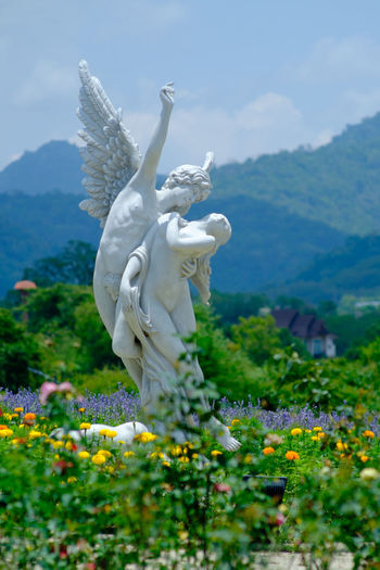 Beauty In Nature Day Flower Human Representation Mountain Nature Outdoors Plant Sculpture Sky Statue