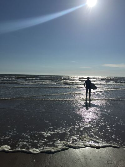 Silhouette of man holding surf on beach