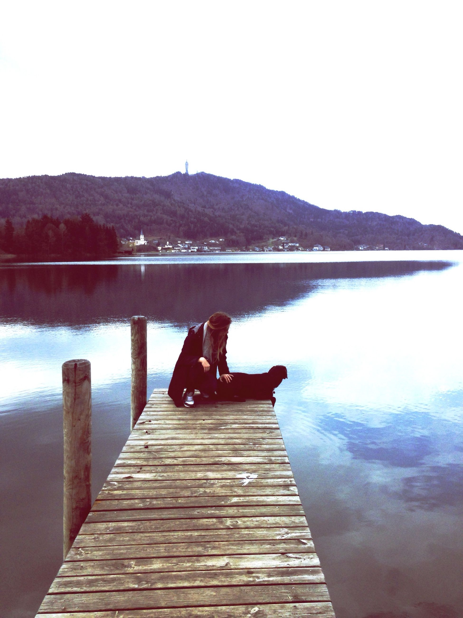 water, lake, lifestyles, leisure activity, sitting, reflection, mountain, men, pier, clear sky, scenics, tranquility, tranquil scene, relaxation, nature, beauty in nature, sky, standing