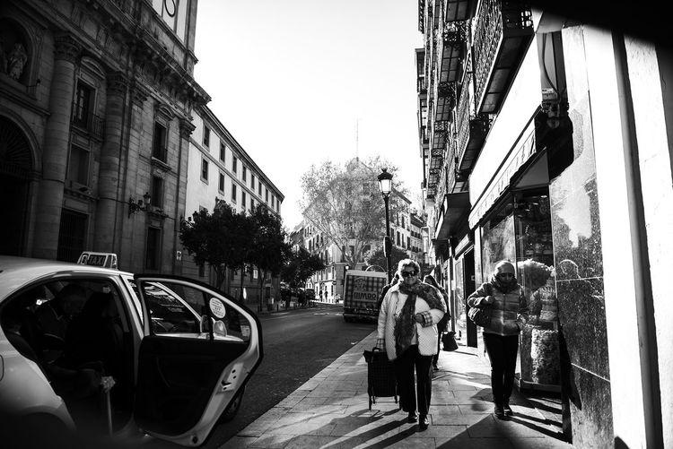 People walking on city street against clear sky