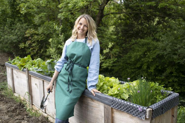 Portrait of a smiling woman standing against plants