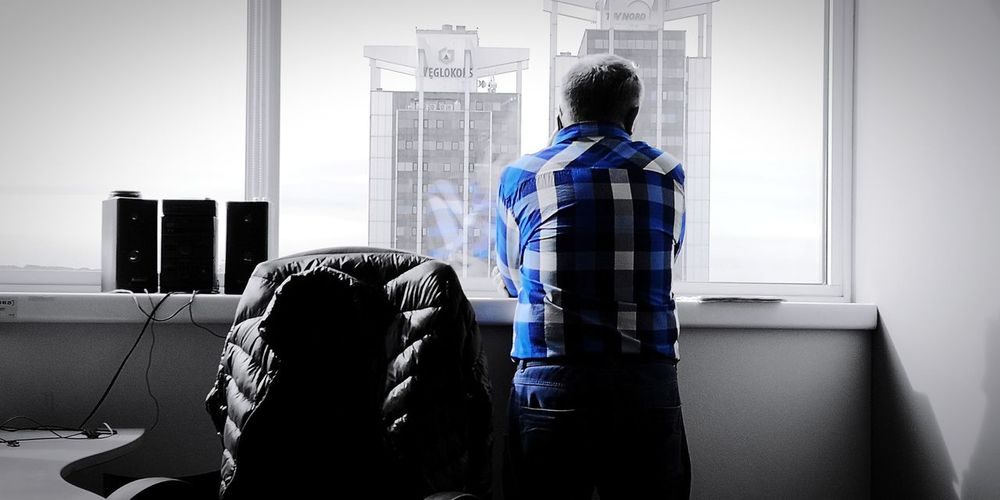 Rear view of man sitting on seat at home