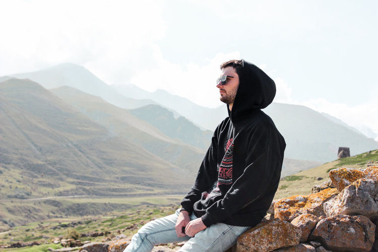 Young man sitting on rocks against sky