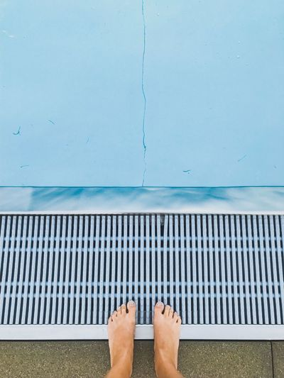 Low section of person standing by poolside